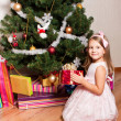 Girl  with gifts near  a fir-tree — Stockfoto