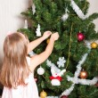 Lovely preschool girl decorating Christmas tree - Stock Photo