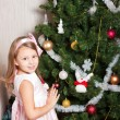 Lovely preschool girl decorating Christmas tree — Stock Photo #4389617