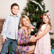 Stock Photo: Mother and children near a fir-tree