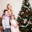 Mother and children near a fir-tree — Stock Photo