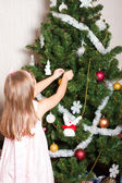 Lovely preschool girl decorating Christmas tree — Stockfoto