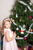 Lovely preschool girl decorating Christmas tree — Stock Photo