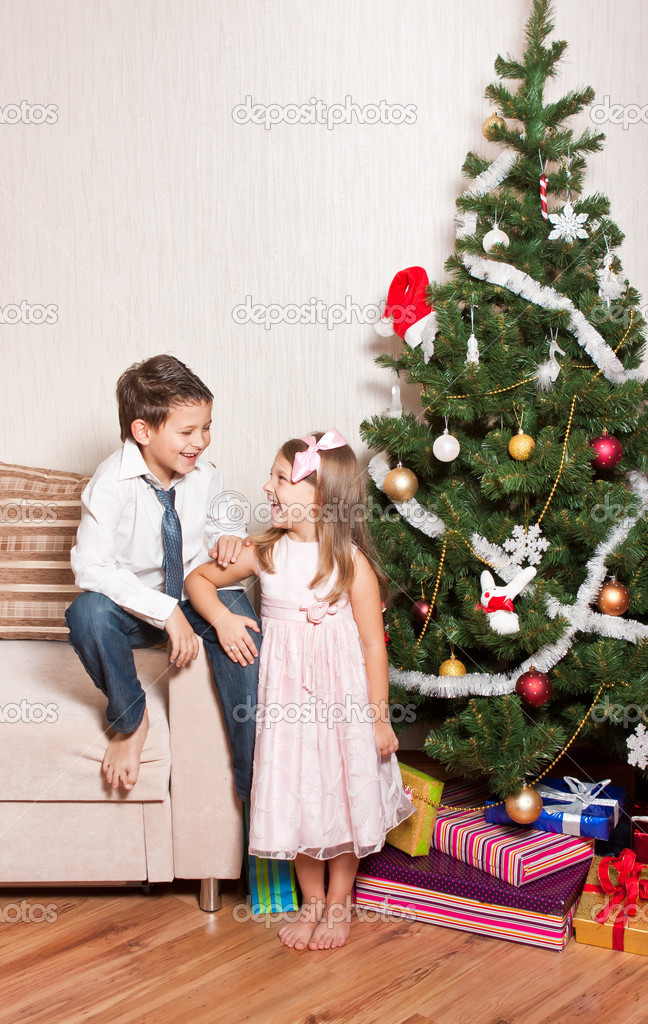 Merry girl and boy with gifts near a new-year tree — Stock Photo #4389488