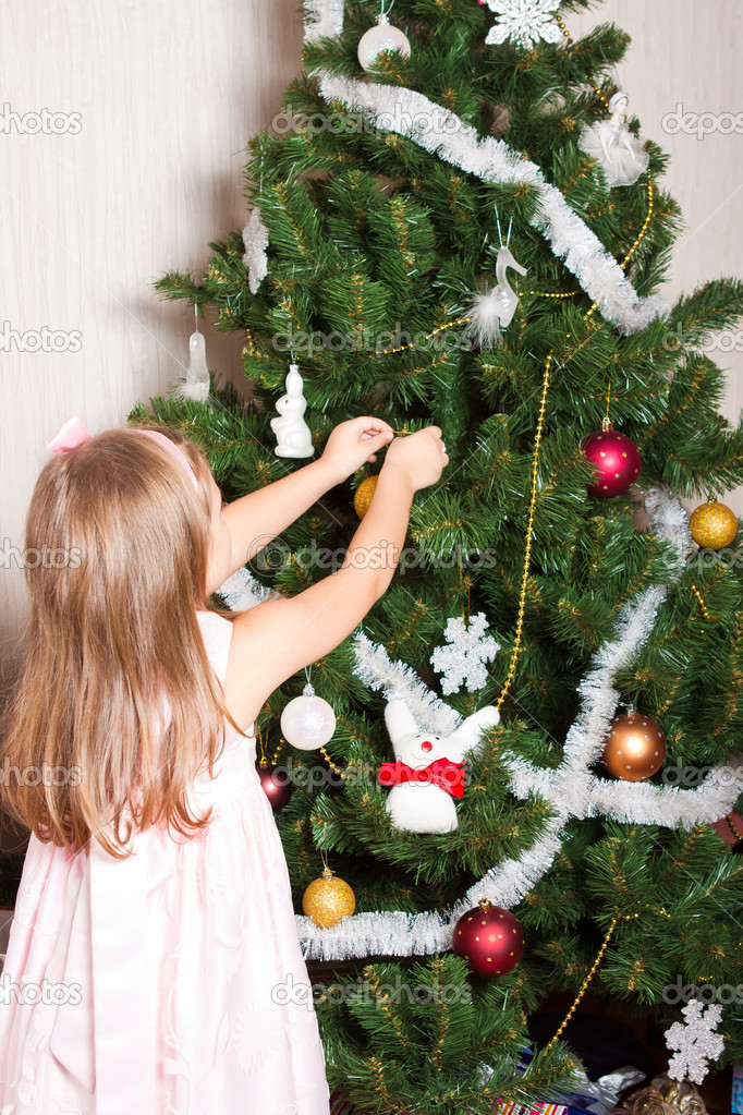 A little girl  decorates  toys a new-year tree  Stock Photo #4389607