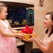 Charming woman gives the gift to her  daughter — Stock Photo