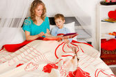 Woman with her son on a bed — Stock Photo
