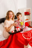 Woman with her son breakfast in a bed — Stock Photo