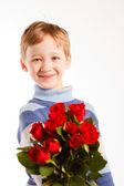 Laughing boy with the bouquet of red roses — Stock Photo