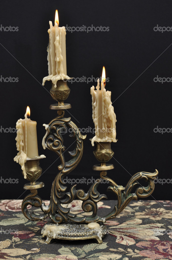Antique candelabra with three melting candles on decorative tablecloth against black background — Stock Photo #5116436