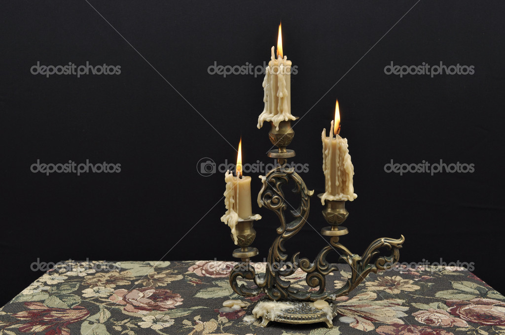 Antique candelabra with three melting candles on decorative tablecloth against black background — Stock Photo #5116440