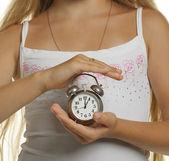 Flickan har en väckarklocka i händerna — Stockfoto
