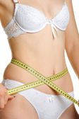 Female shapely a body and a measuring tape — Stock Photo