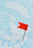 Red flag a pin on blue map — Stock Photo
