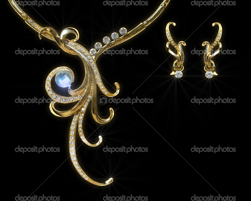 Gold necklace and earring with effect of a luminescence. It is isolated on a black background — 图库照片 #4192774