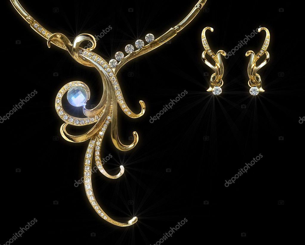 Gold necklace and earring with effect of a luminescence. It is isolated on a black background — Foto Stock #4192774
