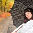 The girl in an autumn wood with a umbrella. — Stock Photo #5198956