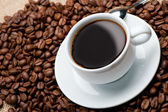 Cup of coffee on coffee grains — Stock Photo