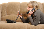 The woman speaking by phone on a sofa — Stock Photo