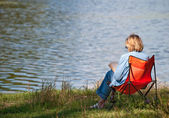 The woman reading the book on coast of lake — Stock Photo