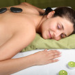 Young woman gets a hot-stone massage — Stock Photo #4106106