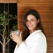 Relaxed woman in a bathrobe at home with tea or coffee — Foto de stock #4329426