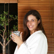 Relaxed woman in a bathrobe at home with tea or coffee — Stockfoto #4329426