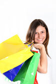 Happy woman comes with colorful bags — Stock Photo