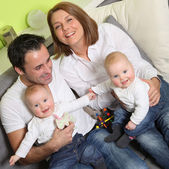Young, happy family with two children and babies - twins at home — Stock Photo