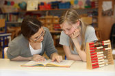 Teacher and student in the school textbook learning together — Stockfoto