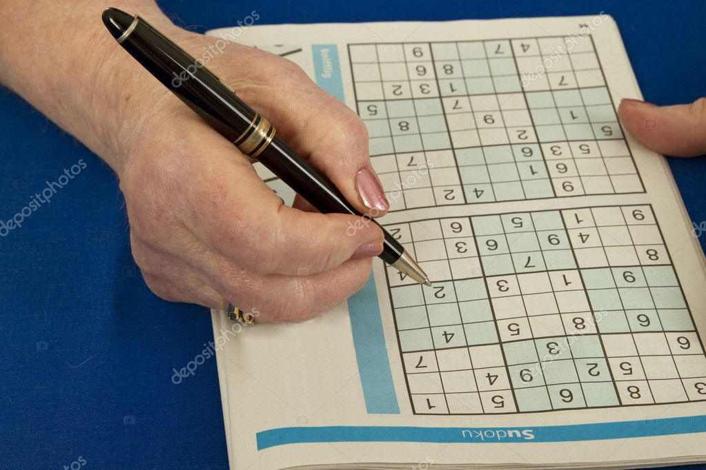 Elderly woman doing sudoku - isolated on white background — Stock Photo #3936921