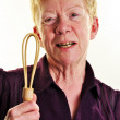 An old age woman is holding a wooden whisk — Stock Photo