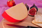 Timber board with some organic gouda cheese — Stock Photo