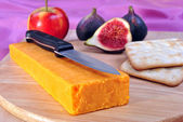 Timber board with some organic cheddar cheese — Stock Photo