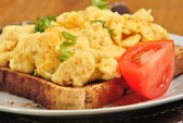 Sandwich with some organic scrambled eggs on a plate — Stock Photo