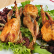 Grilled quails on a plate with salad - Stock Photo