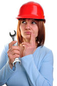 Young woman with helmet holds a wrench — Stock Photo