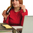 Stock Photo: A young woman drinking at her office desk