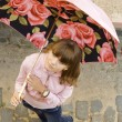 Foto Stock: Girl in pink under the umbrella