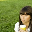 Beautiful girl in the park with coffee — Foto de Stock