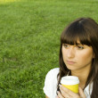 Beautiful girl in the park with coffee — Stock Photo