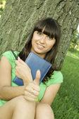 Mujer en un parque con un bloc de notas — Foto de Stock