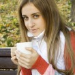 Girl holding coffee cup and smiling — Stock Photo #4054949