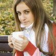 Girl holding coffee cup and smiling — Stock Photo