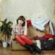 Young woman sits in a suitcase filled with clothes — 图库照片
