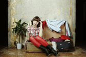 Young woman sits in a suitcase filled with clothes — Stok fotoğraf