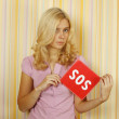 Young woman holding a card with the text of SOS — Stock Photo