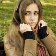 Young woman with headphones in the park — Stock Photo #4685904