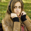 Young woman with headphones in the park — Stock Photo