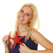 Young woman holds a red starfish — Stock Photo